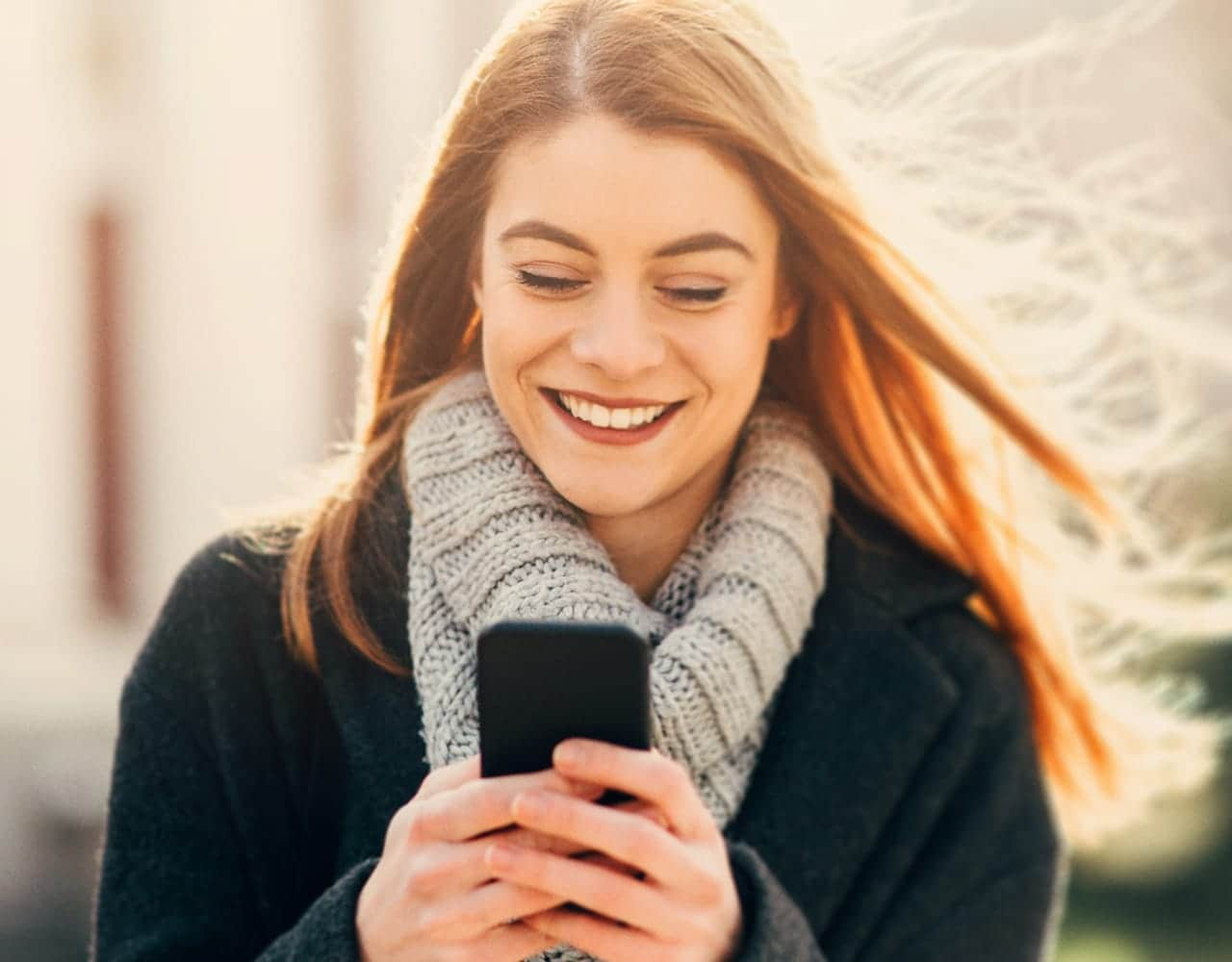 Blond girl with a phone with warm scarf