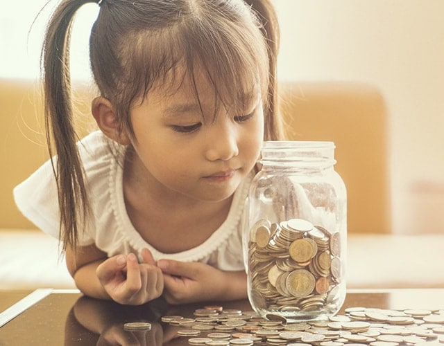 Girl stares at the jar full of money
