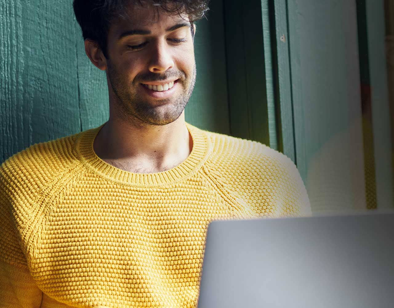 Man in yellow sweater sending money with western union online