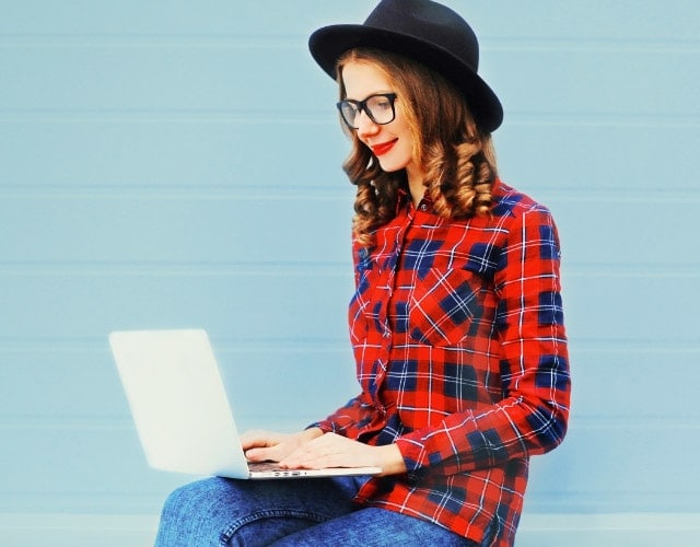 Girl with hat sitting with a laptop on a blue background