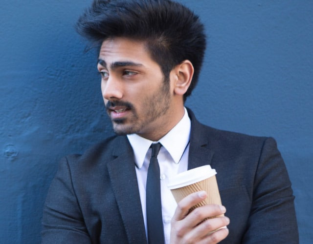 Man in a suit with a coffee cup