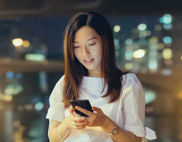 Asian lady in white shirt with smartphone