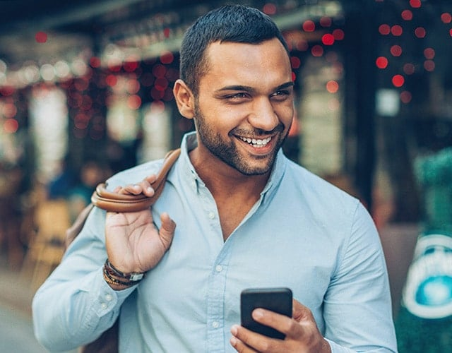 Smiling man with umbrella and iPhone