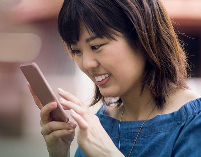 Smiling girl using smartphone